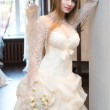 The bride trying on dresses in the bridal salon - Stock Photo