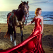 Woman in an elegant red dress with a horse on the beach — Stok fotoğraf