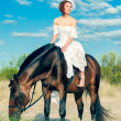 Bride in a white dress walks on the sand with a horse — Stock Photo