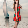 Girl in a dress with poppy enjoys the surf against the backdrop of a sailing yacht - Stock Photo