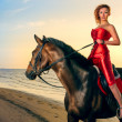 Woman in an elegant red dress with a horse on the beach — Stock Photo #16821395