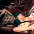 Hot woman in a black sexy lingerie laying on a leather couch - Zdjęcie stockowe