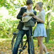 Stock Photo: Couple reading book on bicycle
