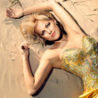 Beautiful girl in a gold-embroidered corset lying on the sand at sunset — Stock Photo #16821639