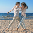 Couple dancing by the sea — Stock Photo
