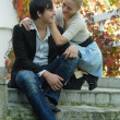 Cute young couple talking in the garden on stairs — Stock Photo