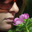 Stock Photo: Girl smelling flower