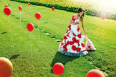 A beautiful young girl standing in the middle of the field balls — Stock Photo