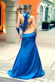 Vacker ung kvinna poserar på gatan visar klänningar — Stockfoto