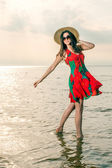 Girl in a summer dress and straw hat dancing on the beach — Stock Photo