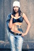 Girl showing her tattoo raised her denim jacket — Stock Photo