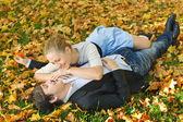 Ungt par liggande på höstlöv — Stockfoto