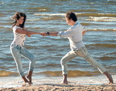 Young couple dancing on a background of sea — Stock Photo