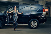 Girl in an underground garage with a car — Stock Photo