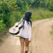 Sexy girl with guitar, standing on a countryside road — Stock Photo #18304637