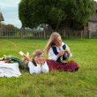 Little boy and girl sitting on a lawn in a national latvian clothes — Stock Photo #18304671