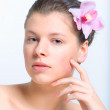 Beautiful female face with healthy skin and flower in hair in spa salon — Stock Photo