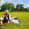 Little boy and girl sitting on a lawn in a national latvian clothes — Stock Photo #18304947