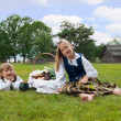 Little boy and girl sitting on a lawn in a national latvian clothes — Stock Photo #18304985