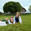 Little boy and girl sitting on a lawn in a national latvian clothes — Stock Photo #18305017