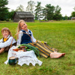 Little boy and girl sitting on a lawn in a national latvian clothes — Stock Photo #18305043