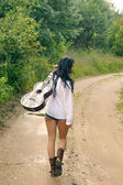 Sexy girl with guitar, standing on a countryside road — Stock Photo