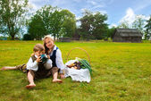Little boy and girl sitting on a lawn in a national latvian clothes — Stock Photo