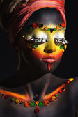 African woman with artistic ethnic makeup on her face and shoulders — Stock Photo
