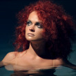 Portrait of beautiful red-haired girl in the water — Stock Photo