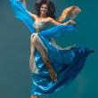 Beautiful girl floating in mid-air, blue silk dress - Stock Photo