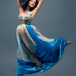Beautiful girl floating in mid-air, blue silk dress — Stock Photo #21589699