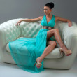 Girl in a turquoise dress lying on sofa — Stock Photo