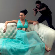 Girl in a turquoise dress lying on sofa - Stock Photo