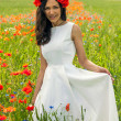 Beautiful young brunette girl wearing white summer dress and flower chaplet in poppy filed — Stock Photo #27915153
