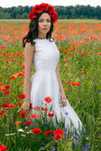 Beautiful young brunette girl wearing white summer dress and flower chaplet in poppy filed — Stock Photo