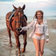 The cute girl with a horse on seacoast — Stock Photo