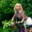 Beautiful young woman portrait with bicycle in the park. — Stock fotografie