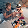 Lovely young couple eating sushi on a yacht — Stock Photo #29054377