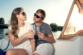Happy young couple drinking champagne on yacht — Stock Photo