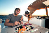 Lovely young couple eating sushi on a yacht — Stock Photo