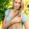 Portrait of beautiful young girl with long blond hair in blue dress in the countrysid — Stock Photo