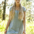 Beautiful young girl with long blond hair in blue dress in the countryside — Stock Photo
