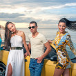 Three girls and a man with sport car — Stock Photo
