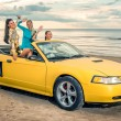 Three girls with sport car on a beach — Stock Photo #30733753