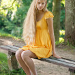 Blond Girl with long hair in yellow dress sitting on a bench — Stock Photo #30948723