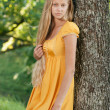 Stock Photo: Blond Girl with long hair in yellow dress leaned the tree