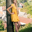 Blond Girl with long hair in yellow dress leaned the tree — Stock Photo