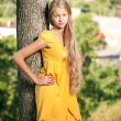 Girl in yellow dress leaned the tree — Stock Photo