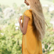 Blond Girl with long hair in yellow dress against rural landscape background — Stock Photo