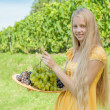 Portrait of a beautiful young blonde holding bowl of grapes — Stock Photo